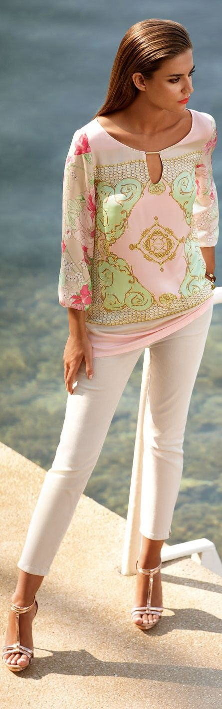 Floral printed medallion top layered over  solid pink scrunched soft knit top,  white capri trousers to be finishing with strappy high heeled sandals.