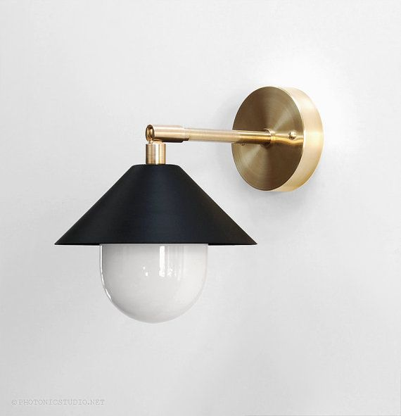 Introducing the UFO sconce, a Photonic Studio original. • Modern wall light • Opal glass diffuser • Cone shade finished in matte black • Solid brass wall plate, arm and fittings. • 10 tall x 7 wide x 9 deep • Six feet of black twisted cloth cord • Inline cord switch and a quality phenolic polarized plug • Porcelain E26 socket. • For use with LED bulbs only. Long-life 40 watt equivalent LED bulb included. 25W or 60W equivalent bulbs can be supplied for an additional $5.00. Minimal, modern...