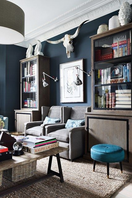 Navy walls with side-by-side armchairs and turquoise stool