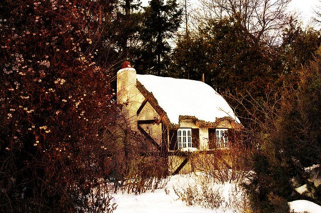 A little thatched cottage, nestled amongst the bracken and dormant trees and shrubs in the English Garden next to the Leo Mol Garden at the city park in Winnipeg.