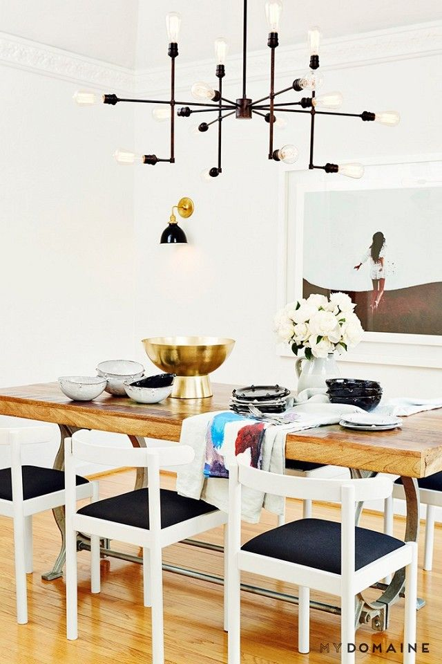 Dining space with a large chandelier, painterly textiles and midcentury modern chairs