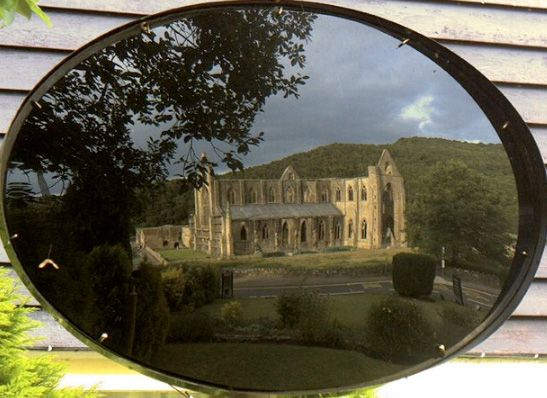 "Tinturn Abbey as seen through a Claude glass, ""a small, tinted, convex mirror that was popular in the 18th century. Toted in artists' cases and tourists' pockets, the portable mirror offered a transformed view of the scenery. It was a picturesque filter for any landscape, reflecting a vista with pleasant distortion and a subtle color palette."" Name of a poem by Michael Ondaatje."