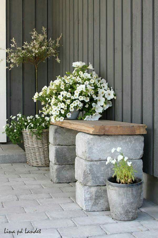Tuin idee: een paar grote stenen en een mooie houten plank. Voor planten / bankje.
