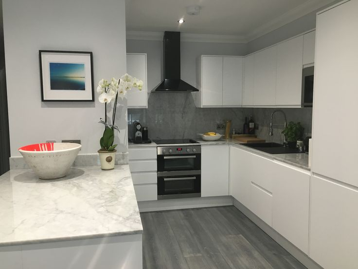Minimal grey, white and black kitchen design. Kitchen with grey wooden floors, matt white cabinets and black features and a soft grey carrera marble countertop