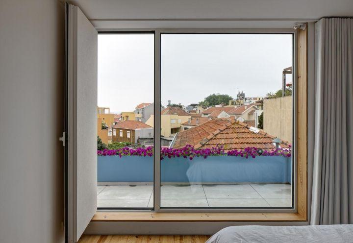 La camera da letto matrimoniale di Flower House affaccia a un ampio terrazzino con vista sui tetti di Porto e sul quartiere di Foz Velha