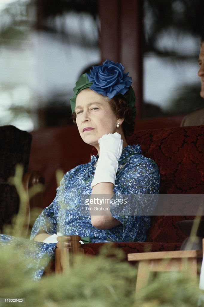 queen-elizabeth-ii-wearing-a-blue-dress-a-blue-and-green-hat-and-a-picture-id116026420