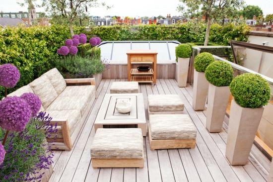 stilvoll Terrasse gestalten Holzbodenbelag - helle Auflagen Gartenmöbel viele Pflanzen Blumen  - Kübel