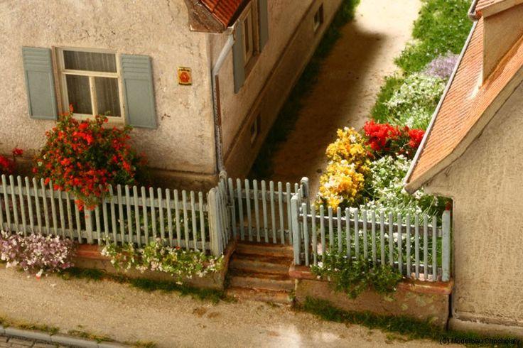 Auf diese Weise lässt sich z. B. ein kleiner Hintereingang zum Hof gestalten. Blütenkissen und Rosenstöcke entstanden mit Silhouette Laubgewebe. Modellbau Chocholaty.