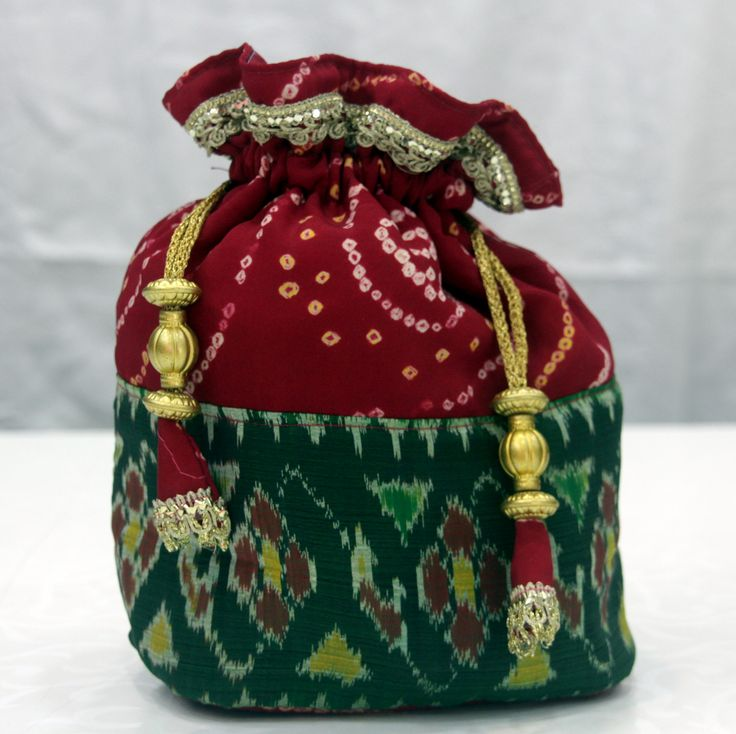 Elegant Bandhani potali bag For fashionistas. Made from 100% handicraft bandhani silk material with resham strings & pretty danglers.     Ocaasion: Marriage, parties.   To purchase visit : http://www.sankalpbandhej.com/  Call/whatsapp: 9377399299