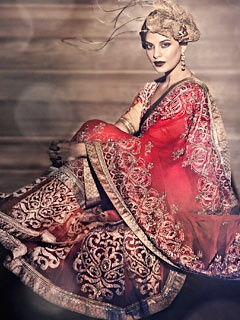 A Satya paul design. Western hair piece on an indian look. works pretty well here. A red sari with prestitched kalidar pleats which are enhanced with dramatic bootis to give a contemporary look. The booties are textured with metallic antique gold gota, combined with a georgette body with ornate antique gold border.