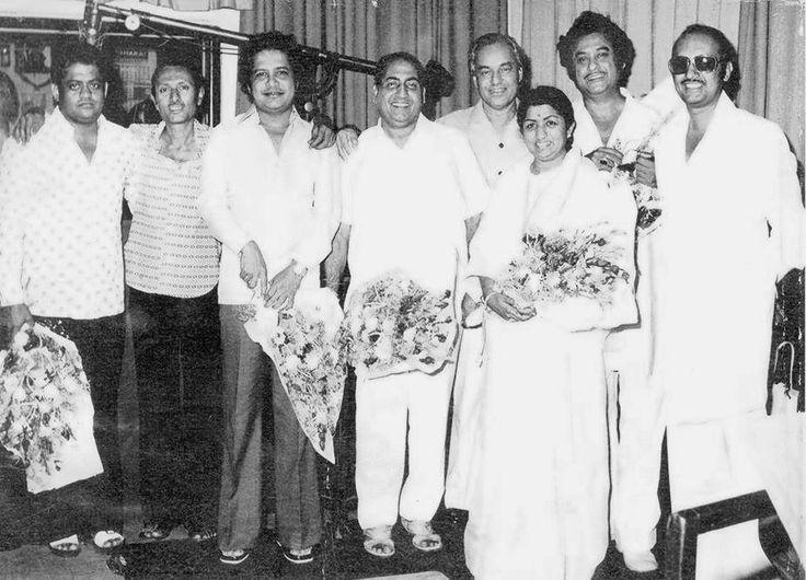 From L to R: Music director Pyarelal, Subhash Desai (Manmohan Desai's brother), Music Director Laxmikant, Mohammed Rafi, Mukesh, Lata Mangeshkar, Kishore Kumar and producer/director Manmohan Desai during the recording session of the movie 'Amar Akbar Anthony' (1977).