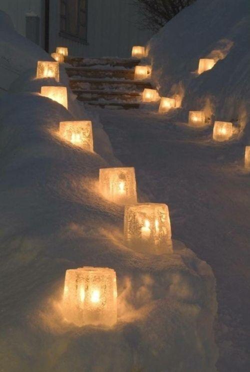 De vraies lanternes en glace guident votre chemin vers l'entrée de la maison