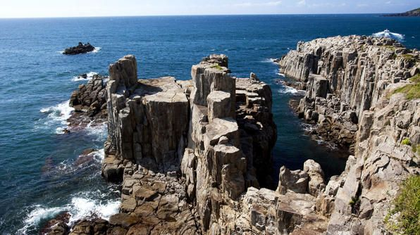 "The series of spectacular rugged cliffs called Tojinbo are almost 100 feet tall and have been designated one of Japan's natural monuments. The tall rock pillars were first formed by ""columnar jointing"" as a result of volcanic activity, and have been shaped by the tumultuous waves of the Sea of Japan."