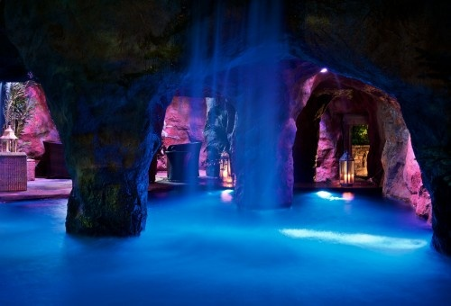 WOW! Multiple waterfalls activated by remote control, a swim-through grotto that leads to a swim-up bar, a kitchen, a flagstone patio with a TV and a sound system, plus a dizzying array of custom light shows created just for the homeowner make this the pool version of a man cave. Caviness Landscape Design