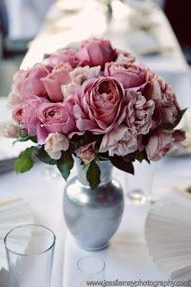 Shades of pink english tea rose centerpiece. We could paint glass vases with metallic silver, find less expensive flower?