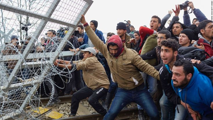 Refugees break through a barbed-wire fence on the Greece-Macedonia border on Monday, February 29, as tensions boiled over regarding new travel restrictions into Europe.