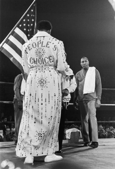 <p> 	Muhammad Ali in an elaborate robe made for him by legendary entertainer Elvis Presley, bearing his slogan, the 'People's Choice' (Isaac Sutton/Ebony Collection)</p>
