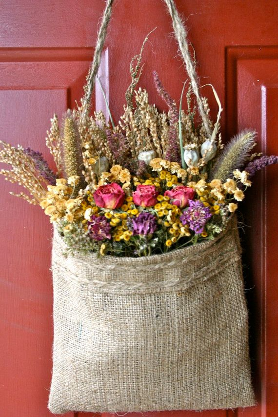 Handmade Burlap Bag filled with dried flowers and herbs...Poppyseed heads, Broom Corn, Coral Roses,Feverfew, Zinnia, Millet and Amaranthus. Perfect for wall decoration or accenting decor. Shades of red,coral and tan. Dimensions 20 tall by 9 inches wide. Works well with most any style of decor, Primitive, Rustic,Cottage, Traditional or Victorian. Pretty as a wall hanger or use as an accent accessary. All flowers are grown by me, free of pesticides.