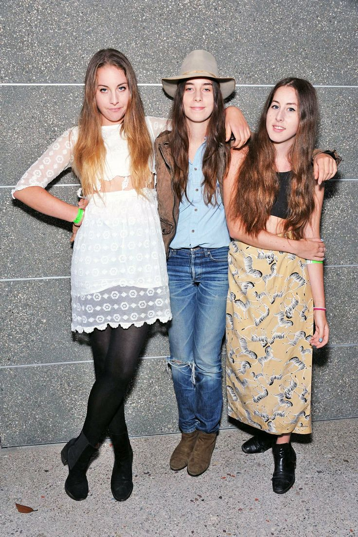 Este and Alana Haim both wear stomach-baring dresses and tops, respectively, while middle sister Danielle Haim styles her well-worn jeans with a blue button-down, fedora, and boots at the Ghost Town: A Party and Art Exhibition benefit in Venice, CA.  Read more: HAIM Style - Fashion Pictures of HAIM - ELLE