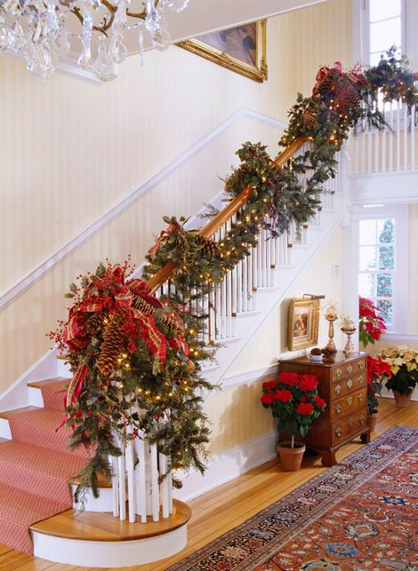 Festive Holiday Staircases and Entryways | Pinecones pop against this pine garland, complemented by the red-and-green plaid ribbon. Small white lights twinkle merrily from within the arrangement. Potted poinsettias line the hallway, guiding guests to the back entrance. | Traditional Home®