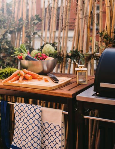 A prep station with a cutting board and lots of vegetables next to a grill.