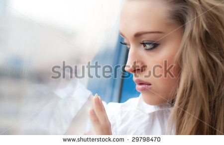 Young sad woman look out a window