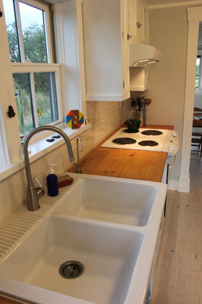Small efficient kitchen, scaled down appliances, like the wood counters: Inside the Beekeeper's Bungalow — thesmallhousecatalog.com