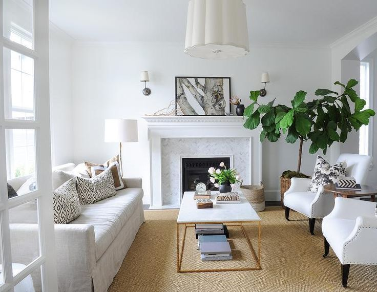 White and brown living room features a Barbara Barry Simple Scallop Pendant illuminating a natural linen skirted sofa lined with black and white pillows as well as brown border pillows facing a pair of white roll arm accent chairs across from a brass and marble cocktail table placed atop a diamond pattern jute rug.