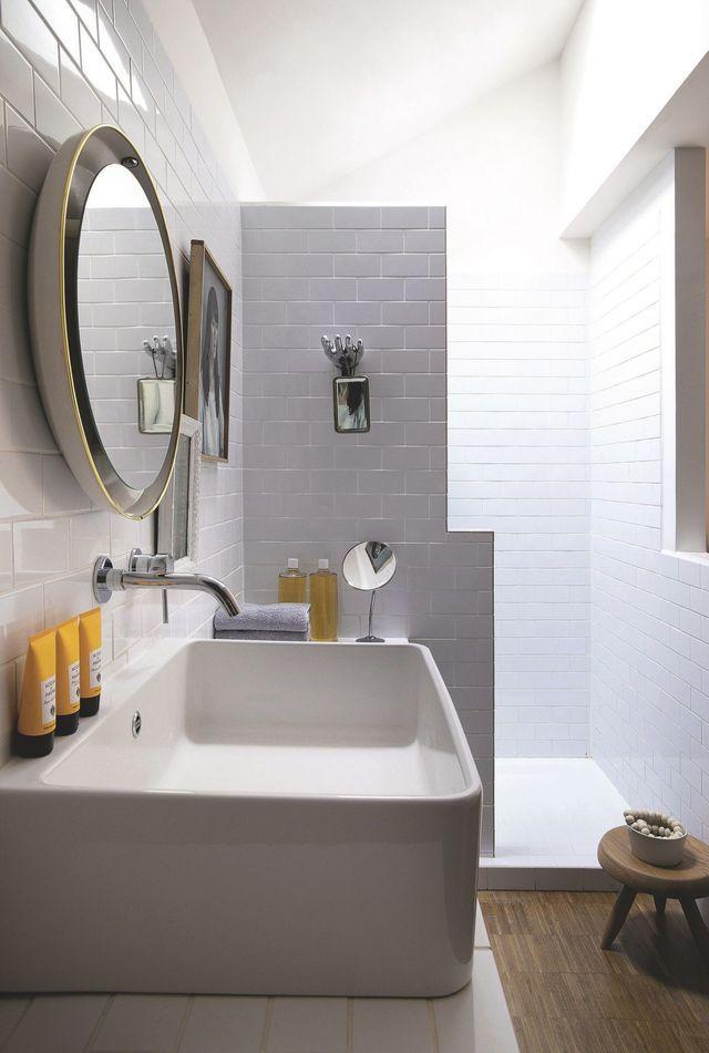 Dans la salle de bains carrelée de blanc style métro, tabouret Charlotte Perriand, portrait et miroirs chinés