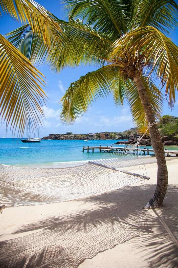 A hammock strung between two palm trees offers a picture-perfect view over the turquoise-blue waters of Galleon Beach on the Caribbean island of Antigua. Photo by: Mirjam Bleeker