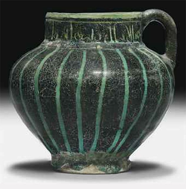 A KASHAN SILHOUETTE WARE TURQUOISE GLAZED POTTERY JUG CENTRAL IRAN, CIRCA 1200 Rising from slightly spread conical foot through squat rounded body to cylindrical neck, simple handle joining neck and body, turquoise glaze with black vertical stripes around the body and calligraphic inscription on mouth