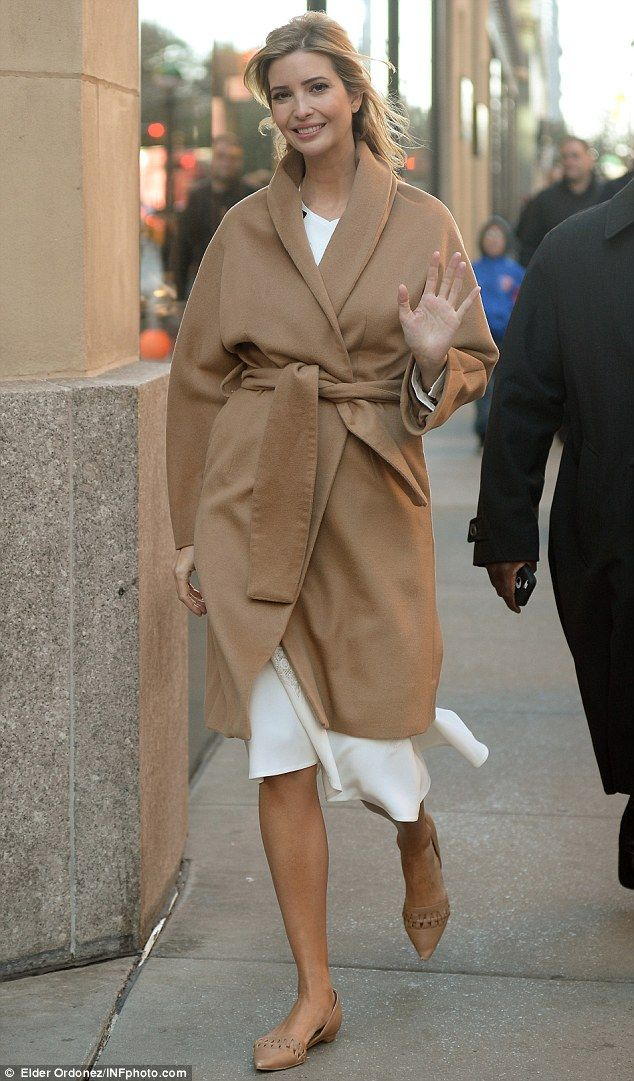 Model attire: Ivanka stunned in a classic camel coat, with a fold-over neckline that covered her white dress.