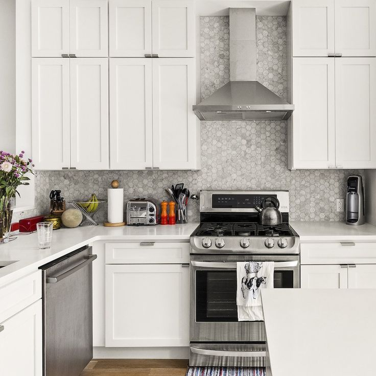 Marsha and Adam decided on an all-white design for their kitchen, complete with Caesarstone countertops, ceiling-height Shaker-style cabinets, and a marble hex tile backsplash that adds a touch of contrast.
