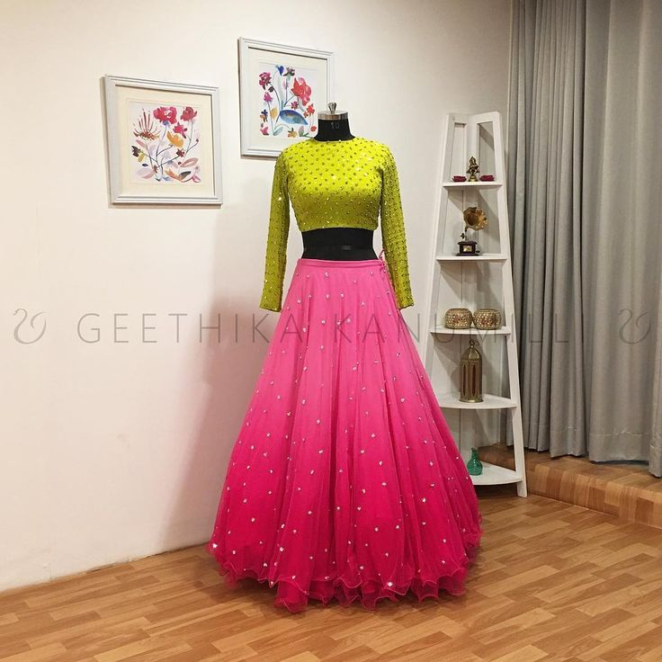 Stunning blush pink color lehenga and parrot green color crop top with full sleeves. Layered lehenga and blouse with buti design hand embroidery work all over. 10 April 2018