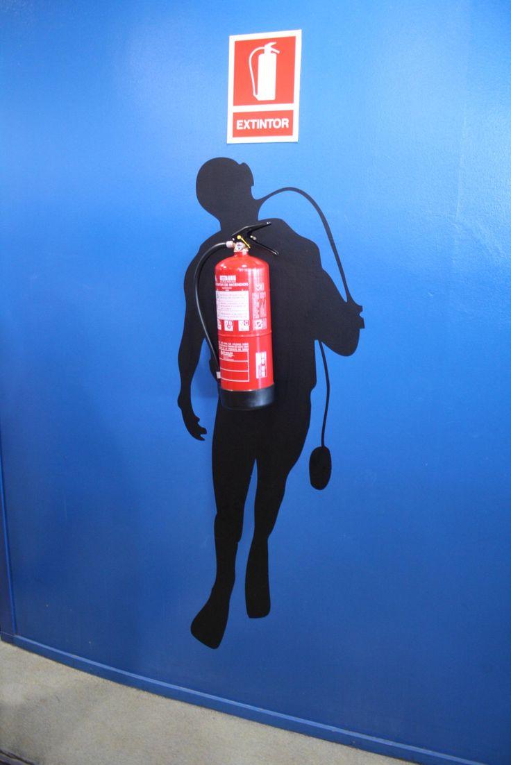 Un plongeur porte un extincteur (décoration murale)