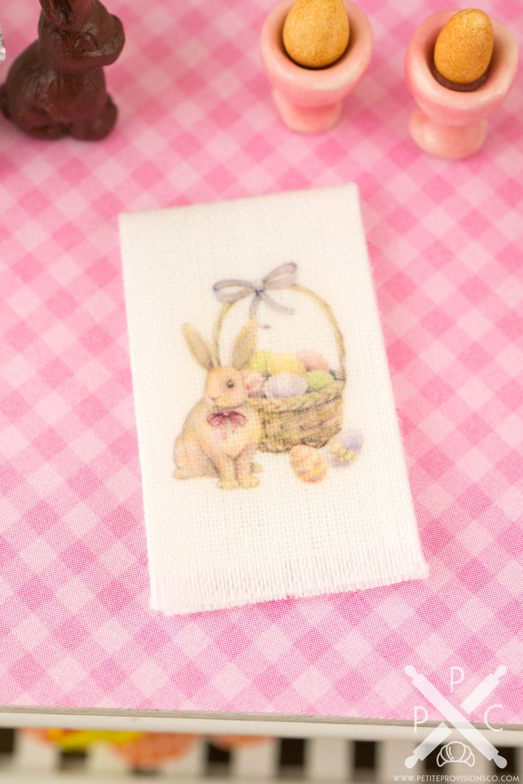 Decorate your mini kitchen and celebrate Easter with this darling little tea towel! This is a white tea towel featuring a watercolor Easter bunny with a basket full of eggs. Whether you have a dollhouse or just love all things tiny, this wee kitchen decoration is too cute to resist!