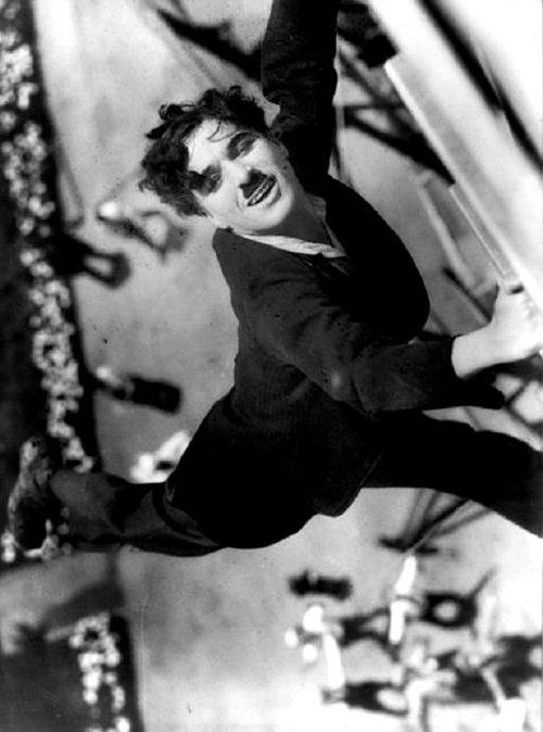 """Charlie Chaplin hanging off the side of a building during production of """"The Kid"""", 1921."""