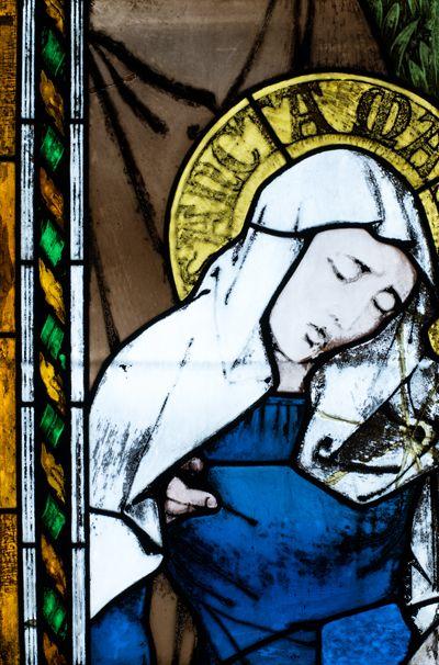Detalj från Sonens fönster: Föreställer Jungfru Maria som svimmar av sorg när hon ser sin son lida på korset. Marias arm och hand hänger slappt vid hennes sida och hennes ögon och läppar är halvslutna. Johannes evangelisten håller henne uppe och hans stödjande hand syns under hennes arm. Maria är avbildad med hustrudok på huvudet, som en medeltida gift kvinna, och iklädd en blå klädnad. Den blå färgen ansågs förutom att vara himlens och konungars färg även symbolisera jungfru Maria.