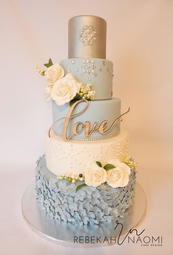 5 tier wedding cake featuring subdued blue tones, ivory and silver. The bottom tier is covered in hydrangea, the next tier features delicate sugar pearls, the top tier features sugar pearls and edible gems. The cake is adorned with gorgeous sugar roses and buds