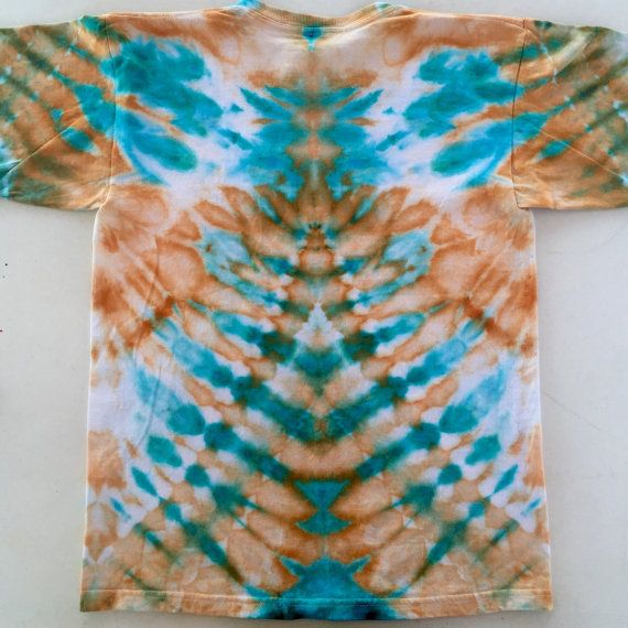 This is a vibrant hand-dyed t-shirt for youths and teens reminiscent a pyramid! Use your imagination to find interesting images in the design. This one of a kind ice dyed item is unique and a great gift for one of the young ones and teens in your life! Colour- Turquoise, Orange, White Size- Extra Large Youth (18-20) Brand- M&O Youth  To create this artistic design ice is used to deposit professional quality dye onto the fabric and the abstract art is created over a period of 24 hours. This…
