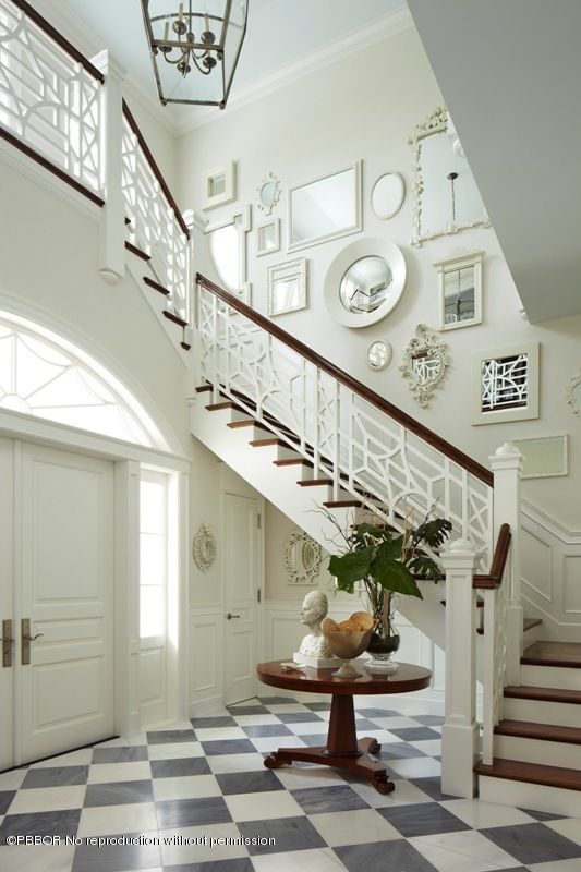 """One can dream.... Beautiful foyer and stairway on posh Banyan Road in Palm Beach. Gorgeous fretwork bannister, lovely grey and white floors, and don't miss the pale blue ceiling. All the cream and white is offset delightfully by the glossy brown wood stair railing and treads. Quirky curation stops this from being too Palm Beach """"typical."""""""
