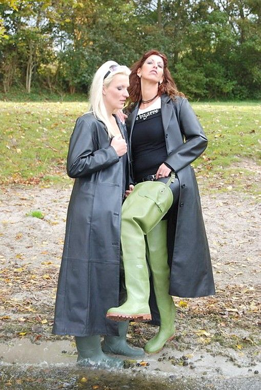 Girls wearing hip waders and rubber raincoats in the mud.