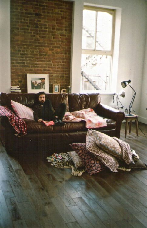 Leather couch, brick wall, cream walls, wooden floor. Studio lamp, picture frames, pillows galore..