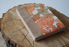 DIY Book, so easy! You'll need Paper or wallpaper for the cover, small piece of craft paper (2.5 x 5 in.) for the spine, recycled bond paper for the inside of the book (cut to 4 x 5 in.) approx 60 sheets, cutting mat, exacto knife, 2 large clips, 2 pieces of thin wood 1x6in., brush, white glue. Directions on website. X