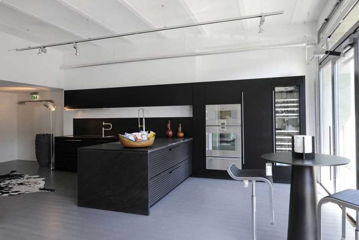 Kitchen tiles black withwhite ceiling and white refrigerator