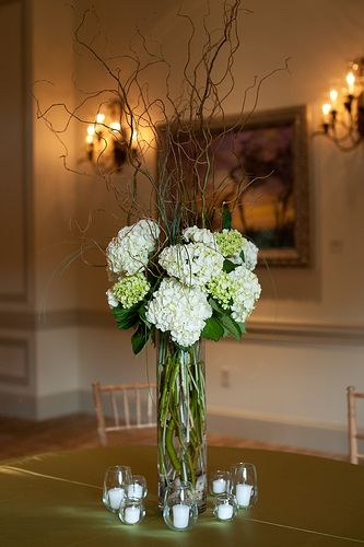 Curly willow, bear grass and mounded green and white hydrangea arrangements