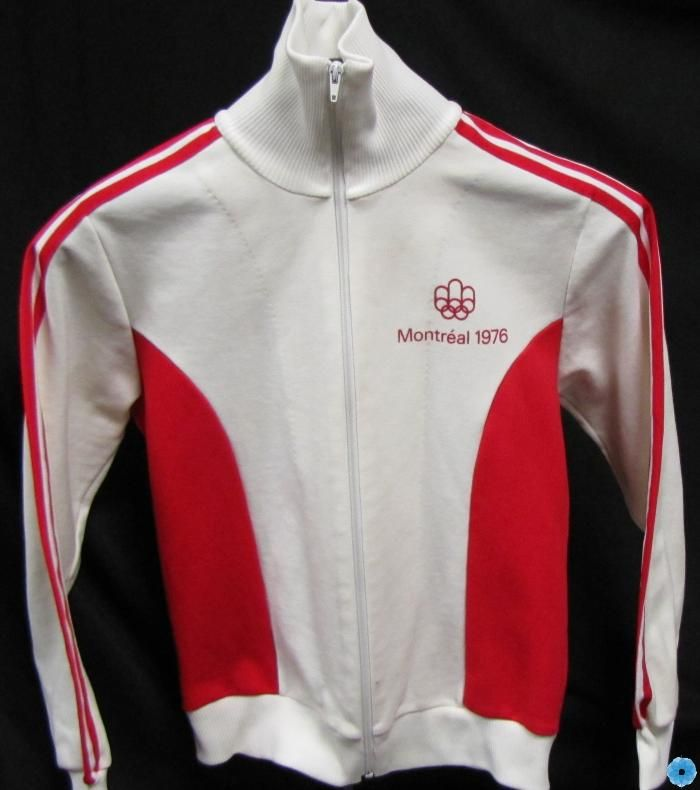 White, zip-front jacket with red accents and logo from the 1976 Montreal Olympics worn by Nancy Garapick.
