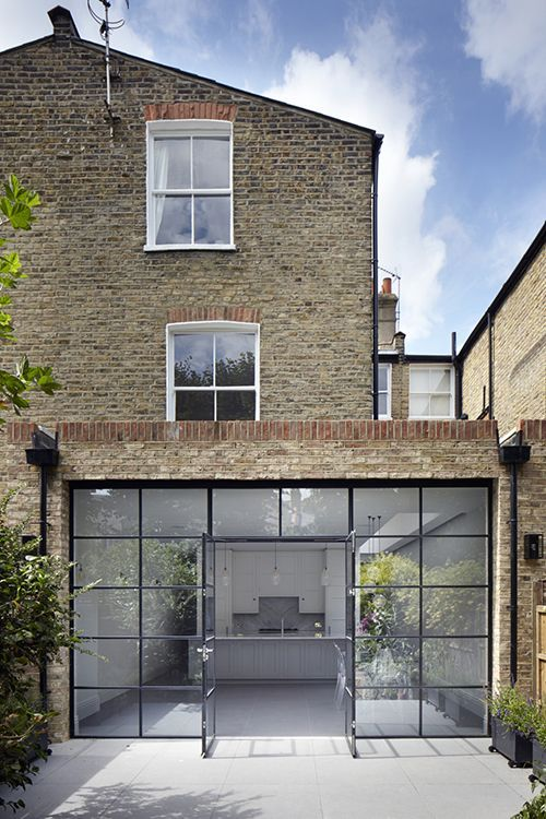 Beautiful modern terraced house design. The kitchen is lit with natural light with a wall completely made of glass.
