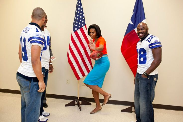 First Lady Michelle strikes the Heisman pose at a Let's Move event in Dallas with Cowboys players Miles Austin, Felix Jones, and DeMarcus Ware. I love the orange and aqua combination!