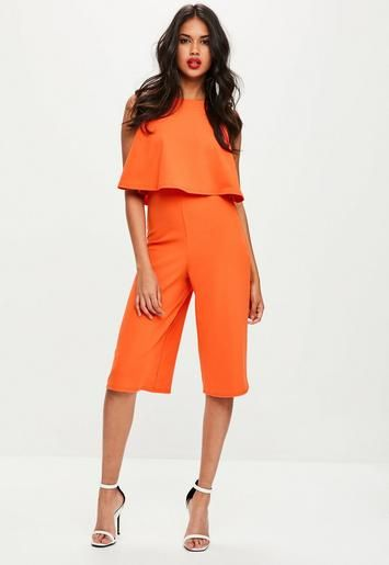 Orange jumpsuit featuring round neck, double layered fabric at the top, open back and culottes design.